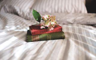 Buch auf Bett - Landhausstiel - Symbolbild